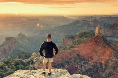 Man standing on edge of Grand Canyon at sunset looking out