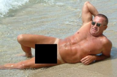 Man sunbathing nude on a beach - penis blacked out