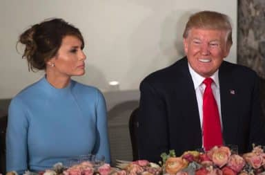Melania sad and Donald Trump smiling at dinner table