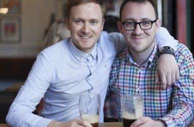 Two men hugging over beers