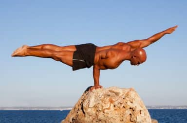 Man balancing horizontally on a rock with one hand
