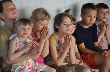 Sad orphan children sitting in an orphanage home