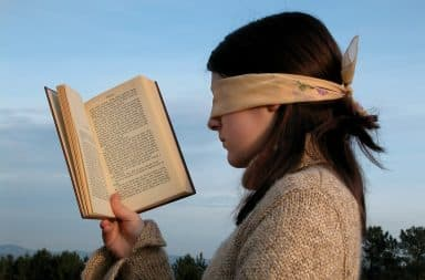 Woman holding book while wearing blindfold