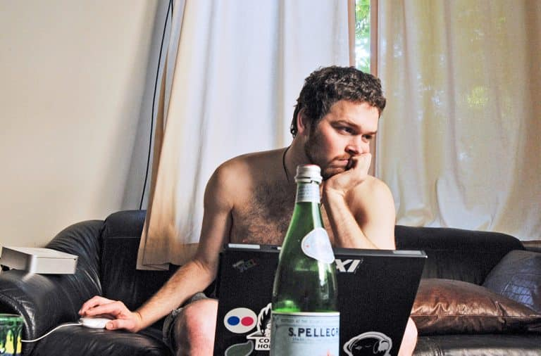 Man working from home naked on the couch