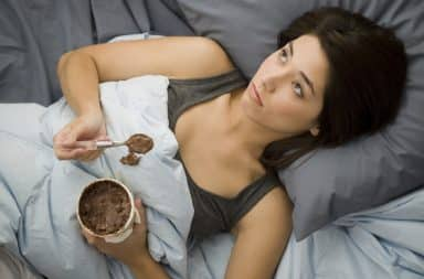 Woman stress eating ice cream in bed