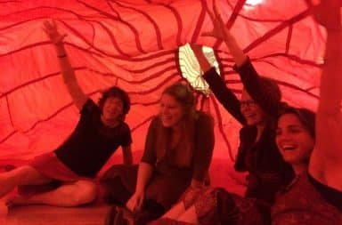 Women inside a red tent camping