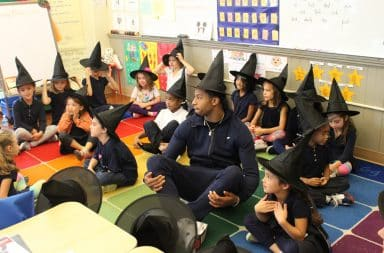Kids sitting in a classroom wearing witch and wizard pointed hats