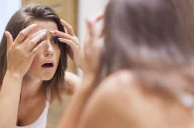Girl popping pimple in the mirror