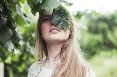 Woman rubbing her face on leaves of a tree for a beauty routine