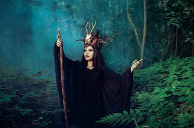Female witch holding a scepter in the woods