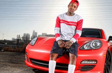 Rapper sitting on a fancy red Porsche car