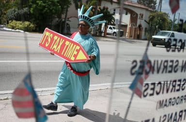 "Tax man wearing Statue of Liberty costume with ""Tax Time"" sign"