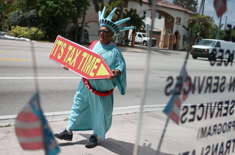 """Tax man wearing Statue of Liberty costume with """"Tax Time"""" sign"""