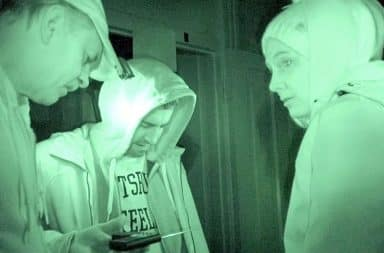 Ghost hunters using night vision while exploring paranormal activity