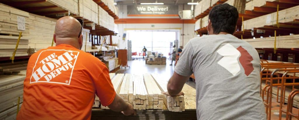 Home Depot employees pushing wood on a cart in the store