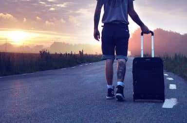 Man wearing jean shorts walking his suitcase down the road into the sunset