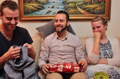 Cousins opening gifts together on the sofa at Christmas
