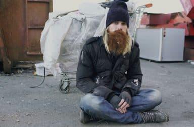 Drunk homeless man sitting next to a pile of garbage