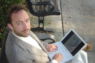 Jimmy Wales sitting down with laptop in his lap