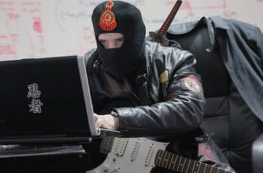 Ninja holding a guitar at a laptop computer