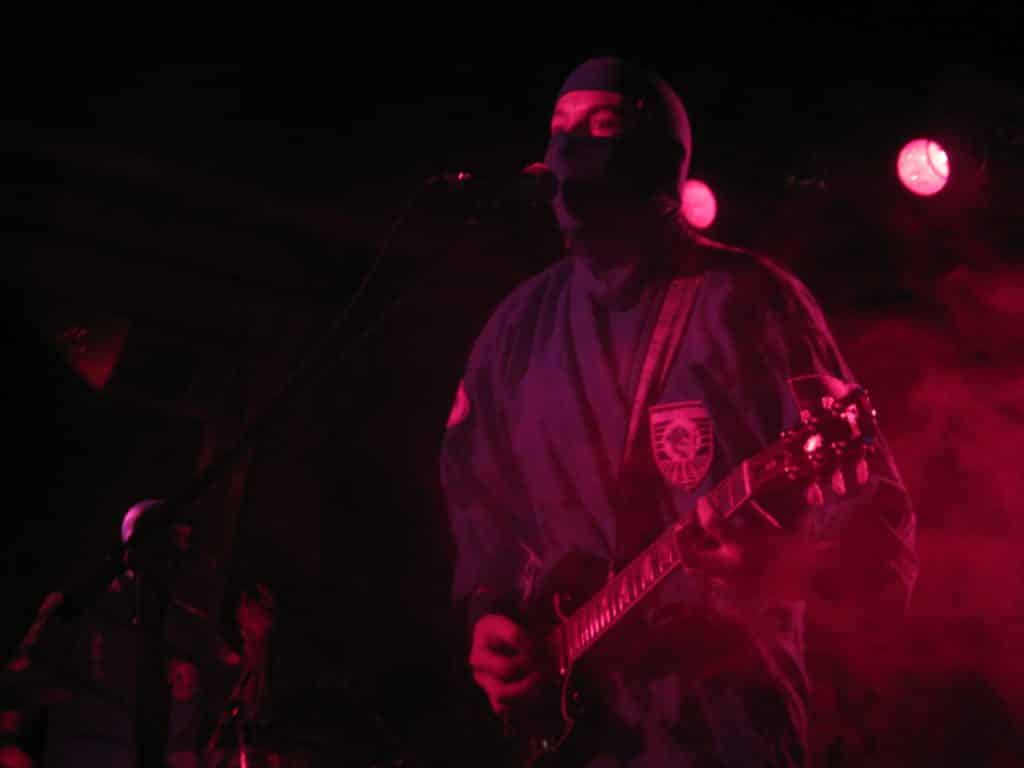 Guy dressed as a ninja playing guitar on stage