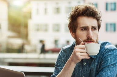 Man drinking coffee looking away