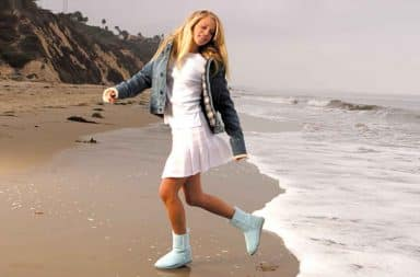 California girl wearing Uggs on the beach with waves