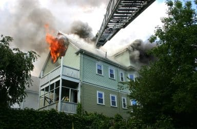 Fire ladder from fire truck reaches house on fire