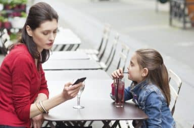 Mom texting with her daughter at a table outside