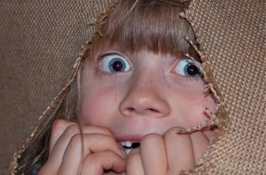 Scared child peeking out of a burlap bag