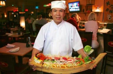 Japanese chef holding a wooden sushi boat