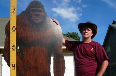 Man with his hand on the shoulder of a large Bigfoot cardboard cutout