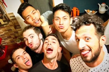 Guys at a Grindr house party smiling