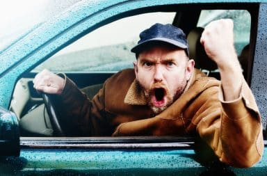 Man holding his fist out the open window of a car angrily