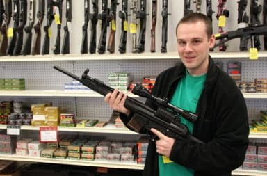 Man holding an automatic rifle in a gun shop at a shopping mall