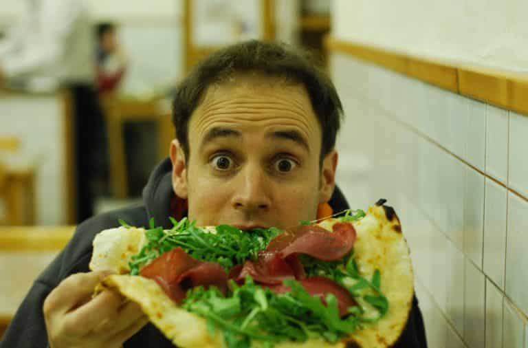 Man eating pizza with guilty look on his face