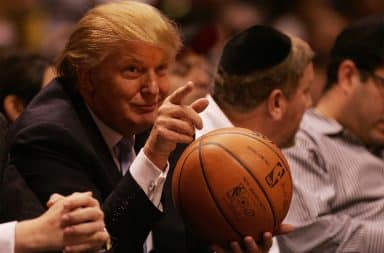 Donald Trump holding a basketball at an NBA game