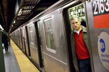 Man looking out of a subway car suspiciously