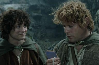 Sam checks his phone and Frodo looks on