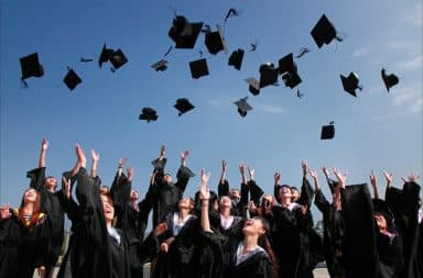 College students tossing graduation hats into the air