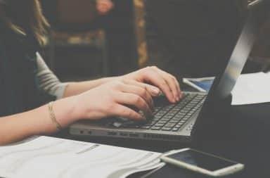Woman typing at a laptop keyboard