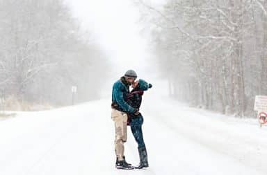snowy couple risking getting hit by a plow, honestly, get out of the road!