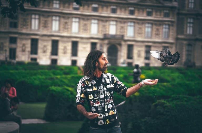 Hippie man feeding pigeon
