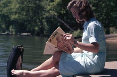 Woman reading Playboy magazine on a boat dock