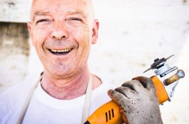 Dad holding a power saw and smiling