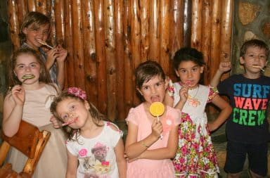 Kids eating lollipops at a party