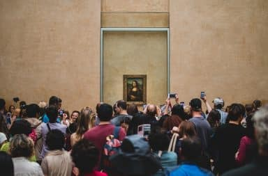 mona lisa, by da vinci, and surrounded by people, why is she smiling? history's mystery i guess