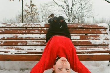Girl upside down on a bench in the snow