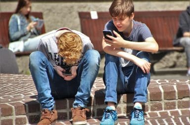 Two boys sitting on the curb together