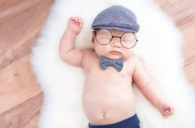 Baby wearing trendy eyeglasses and a hat